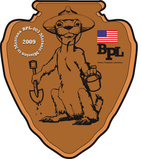 Custom Mission Patch. The official BPL-003 Moranic Mission To Montana emblem.  Features 'arrowhead' motif with cute pest rodent handling collection equipment, in true space mission design tradition.